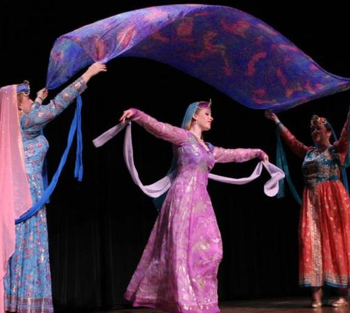 Stage performance of Persian dance. Two women hold a chunni above the head of a woman dancing in between them. They all wear colourful full-length, full sleeves clothing.
