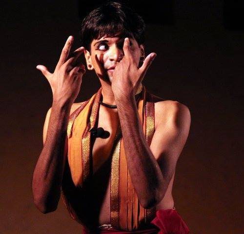 A boy performing Bharatnatyam on stage. He wears kajal, and an orange dupatta hung around his neck falls from both sides till his waist. The photo ends at his torso.