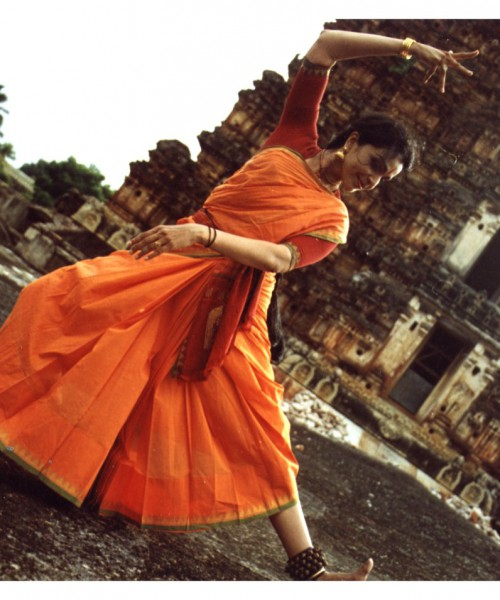 Anita Ratnam in an orange saree doing Bharatnayam outside an old temple.
