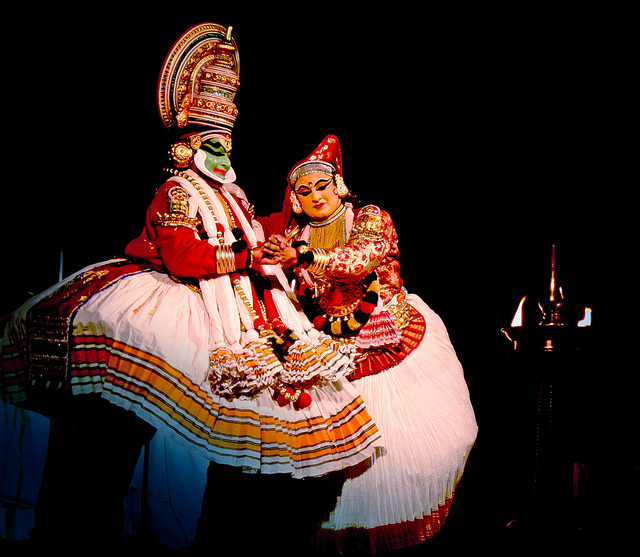A man and a woman perform Kathakali on stage, wearing typical Kathakali costumes of red and white and elaborate headgear. A lamp is lit on the stage. Their makeup and dresses show beautifully in contrast to the darkened stage.