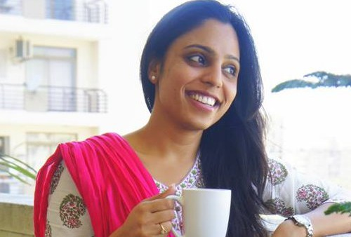 A young woman in a white Indian suit and red chunni standing on a balcony with a coffee mug in her hands. Her hair is let down and pulled over the left shoulder. She is smiling broadly.