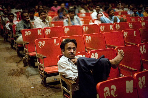 A man sits leisurely with his legs on his chair in a theatre. The audience chairs are coloured red, and are numbered. Many more men who are out-of-focus in this picture sit in similar fashion in rows behind him, looking at the screen.