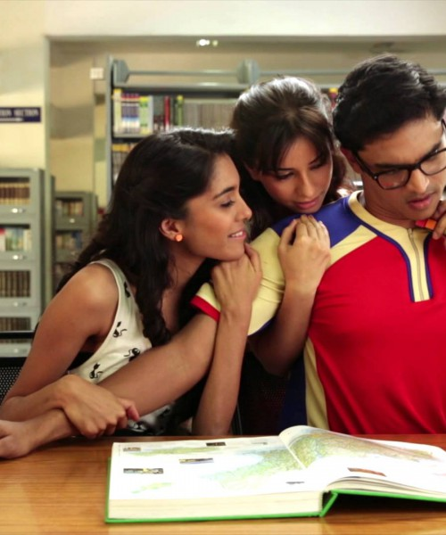 """Clip from an Axe Effect advertisement. A boy reading in a library, experiencing the """"Axe Effect"""". Two girls are attracted towards him, hugging him from his shoulder. He is wearing blue tee shirt and glasses."""