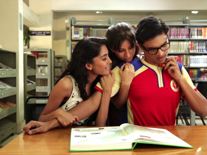 "Clip from an Axe Effect advertisement. A boy reading in a library, experiencing the ""Axe Effect"". Two girls are attracted towards him, hugging him from his shoulder. He is wearing blue tee shirt and glasses."