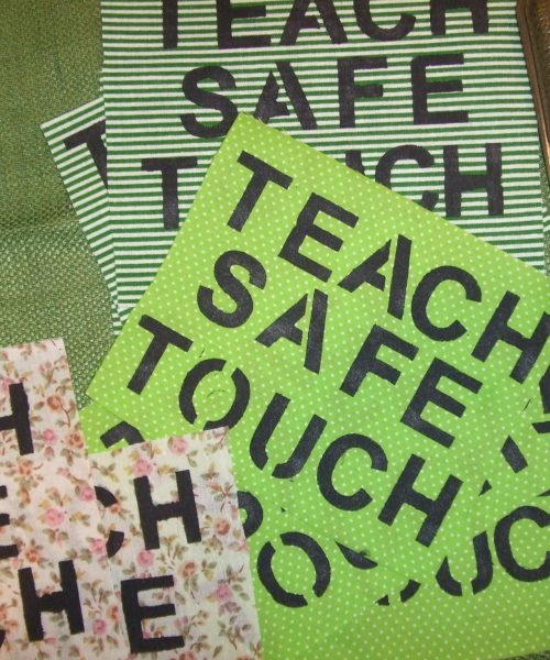 A series of pink and green placards that read 'Teach Safe Touch'