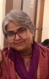 Headshot of psychologist Sadhna Vohra, she has white hair and dark glasses and is wearing an orange dupatta around her neck