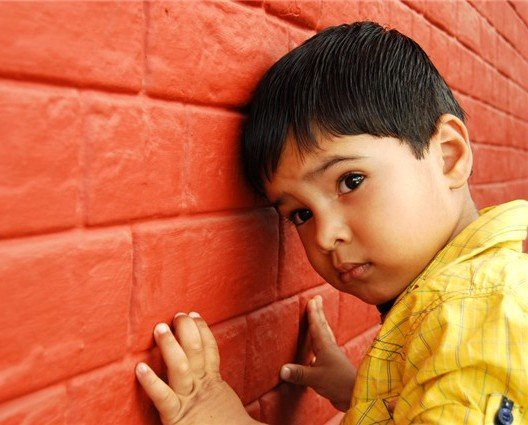 A male child dressed in a yellow shirt leaning against a red brick wall