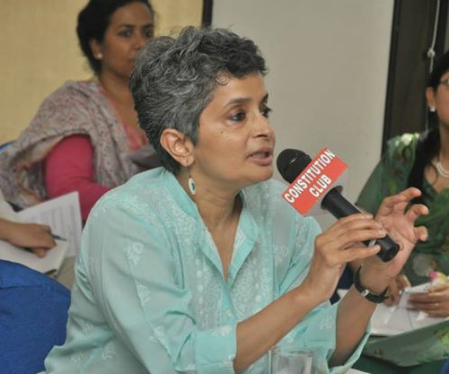 Nivedita Menon speaking into a mike of Constitution Club at a gathering. She is wearing a green kurta, and earring. She and others are sititng on ground cross-legged.