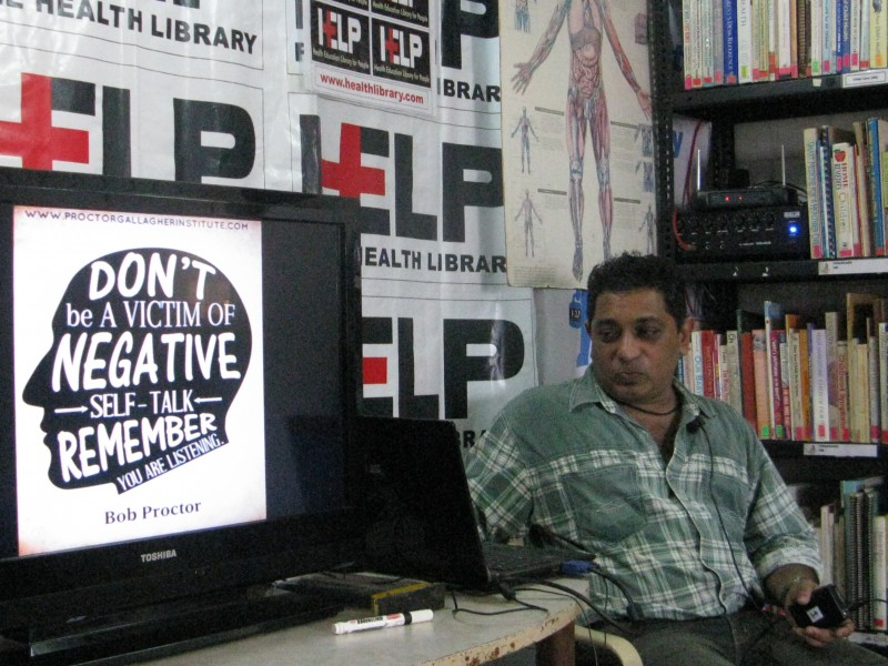 A man in a checkered shirt sits at a dek where a placard shows the rough outline of the human brain with messages about the importance seeking help for bad mental health written on it