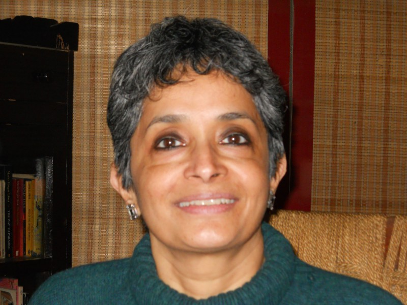 Nivedita Menon, wearing a green turtle-neck sweater, sitting on a chair, smiling.
