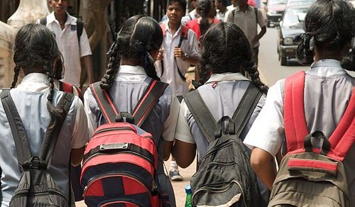 Children going to or returning from school. The focus is on four girls in grey and white school uniforms, wearing two braided plaits, and school bags on their shoulders, walking with their backs to us.