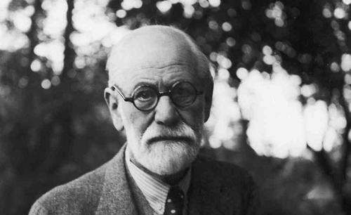 Black and white picture of psychologist Sigmund Freud. He has a white beard, is wearing dark round glasses along with a tweed jacket