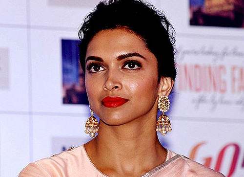 Headshot of actress Deepika Padukone. Her hair is tied back in a bun, and she is wearing gold earrings and a pastel pink salwar.
