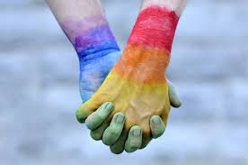 Picture two hands holding each other, with rainbow colours painted on them