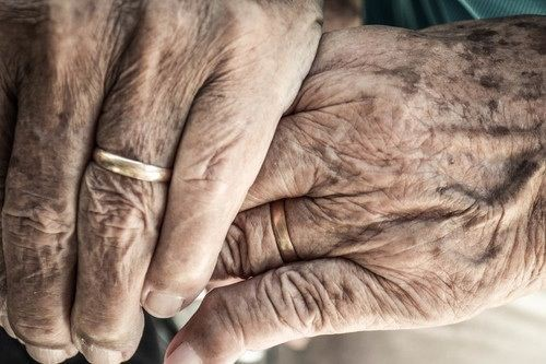 A pair of hands with wrinkles on them holding each other. One of the hands is wearing a gold band on their ring finger