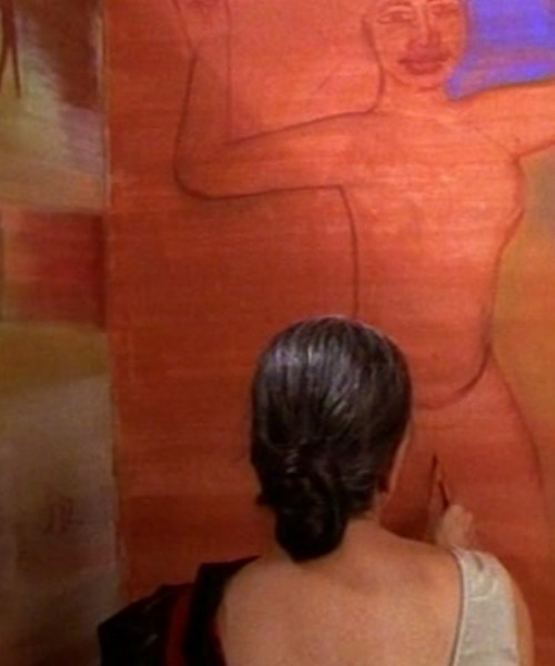 A woman in a black saree and white blouse faces a red wall, so that only her back is visible