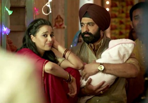 Still from film 'Tanu Weds Manu Returns'. A woman and a man in a wedding. The man holds a baby wrapped in a white cloth in his arms. The woman wears a red Indian suit, red bangles, and has open hair. The man wears a red turban and golden kurta.