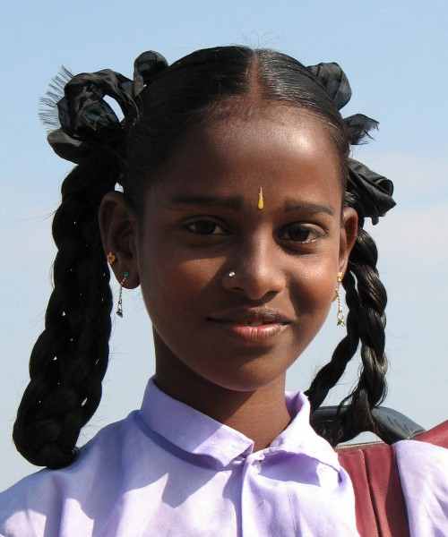 Photo of an Indian girl in a school uniform, carrying her schol bag on her shoulders. Her hair are neatly set in two braids, tied with a black ribbon.