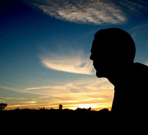 Silhouette of a man sitting in an open landscape. Sunset, windy weather, and cloudy sky could be seen behind him.
