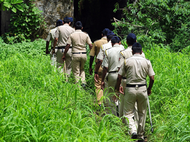Some ten policemen in uniforms walking through a jungle in a queue.