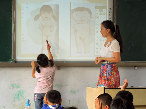 Photo of a class studying anatomy. A little girl pointing to the vagina of the person in the projected image on the board. The teacher stands on the side, looking on.
