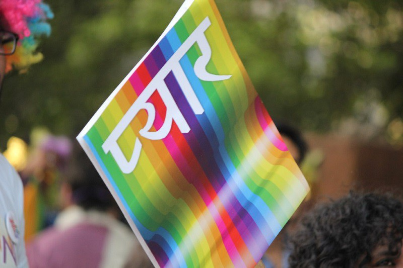 "A placard reading ""pyar"" (love) in Hindi in white lettering on a rainbow-coloured background."