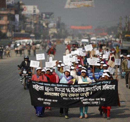 "Nepalese women on a protest march. They are carrying a poster that reads in Hindi, ""Women Against Violence Day"". They are wearing white caps, and holding placards."