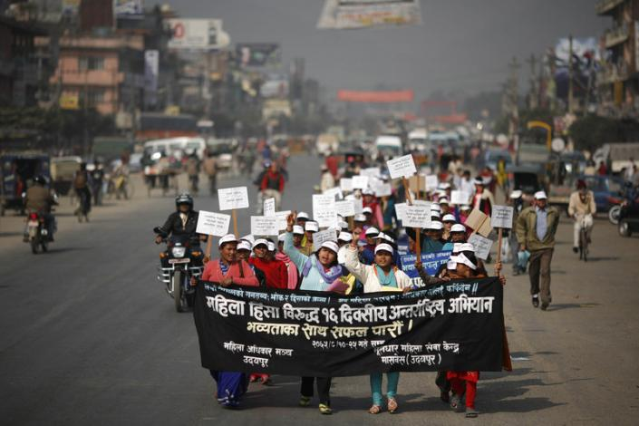 """Nepalese women on a protest march. They are carrying a poster that reads in Hindi, """"Women Against Violence Day"""". They are wearing white caps, and holding placards."""