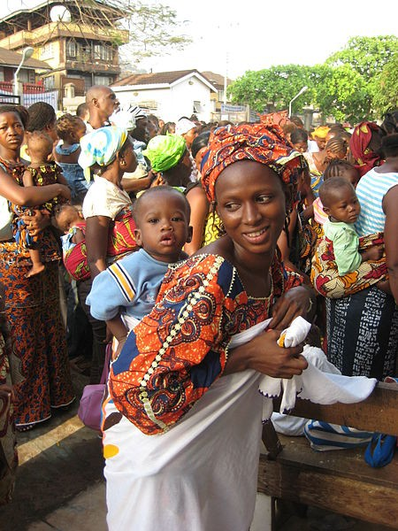 Photo of several African women wearing colourful clothing carrying babies on their backs.