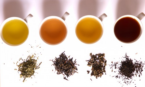 Four cups of different flavoured teas kept in a row horizontally. Next to each is kept corresponding dry tea leaves.