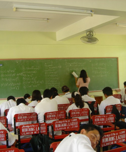 Classroom. A teacher writing on a board, and girls and boys in white school uniform are sitting looking down at their books.