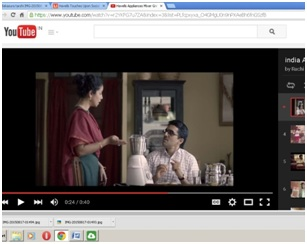 Screenshot of a YouTube page. The video still shows a husband sitting at a dining table. His wife stands nearby, talking to him, pointing to a mixer kept on the table.