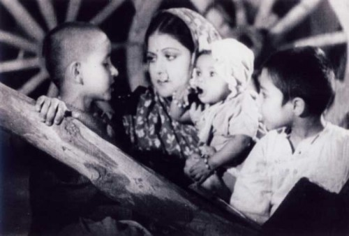 """Still from a black and white Indian film, """"Aurat"""" (1940). A mother with her three kids."""