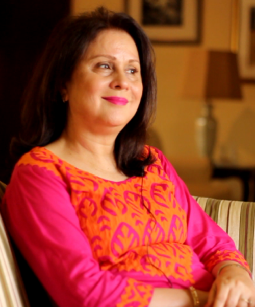 Uzma Noorani, a human rights activist, sitting on a sofa smiling. She is wearing an orange and pink Indian suit, and has her hair falling on her shoulders.