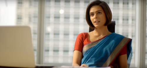 A young woman in a blue saree and red blouse sitting in her office chair, with a laptop open in front of her. Skyscrapers are visible through the glass walls behind her. She has a short haircut.