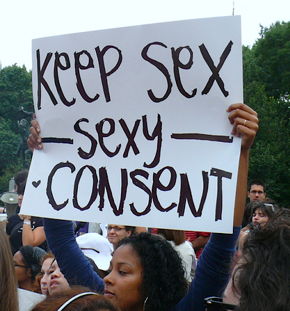 """A brown woman in a blue top standing amongst a crowd raises a placard that reads in black on a white background, """"Keep sex sexy - consent."""""""