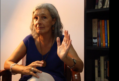 Alejandra Sardá-Chandiramani in her house. Sitting on a chair, she is talking with hand gestures to explain something. There's a bookshelf peeking from the left side of the picture.
