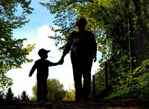 Silhouette of a woman with a little boy walking in a park, hand in hand.