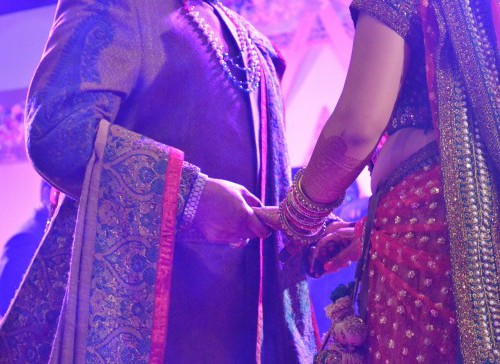 A bride and her mother holding hands face-to-face during the wedding celebration. Their faces are cut from the picture - we can see from their neck to their knees, dressed in a bride's lehnga, and a heavy Indian suit.