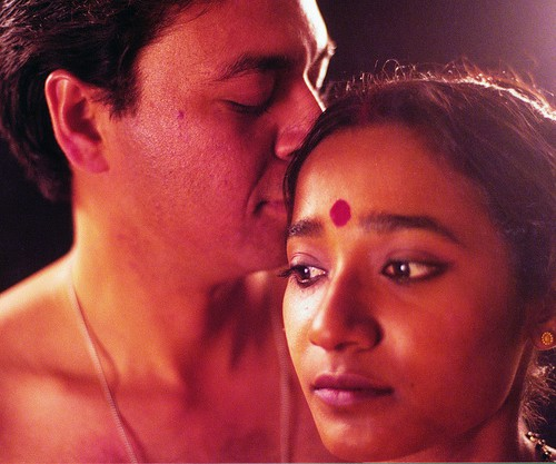 "Still from film ""The Lovedance"" (2000). A bare-chested man smelling a woman's hair from behind. She wears a red bindi on her forehead."