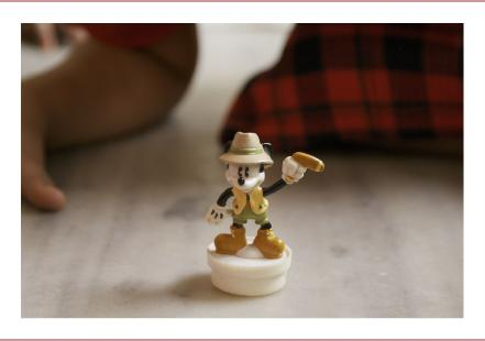 A toy figurine of Mickey Mouse. Hands and knees of the child kneeling around it to play with it are visible in the background.