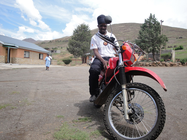 A black man in a white shirt and black pants sitting on a motorcycle in a peaceful hilly town.