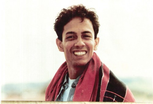 Dominic D'Souza, a young gay man. He is smiling at the camera. He wears a white vest peeking through this black-and-white striped shirt, and a red shawl thrown around his shoulders.