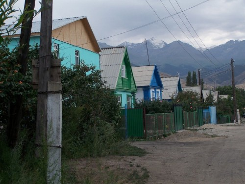 Street with tin roof houses in a hilly area. Snow-capped mountains can be seen behind.