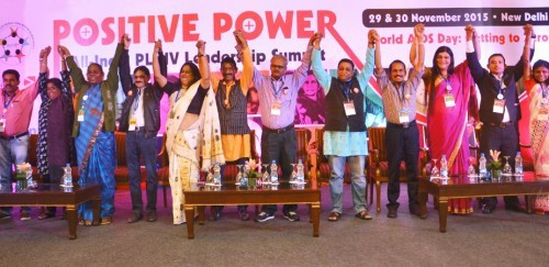 "Professionals standing in a row on stage. They join their hands and raised them up in celebration. The poster on the wall behind them reads, ""Positive power""."