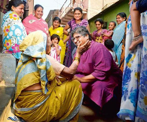 Meena Seshu squatting on the floor as an older woman sitting on the floor caresses her on the cheek. Several women stand around them, looking on. Seshu is wearing a purple kurta, and the older woman wears a yellow saree.