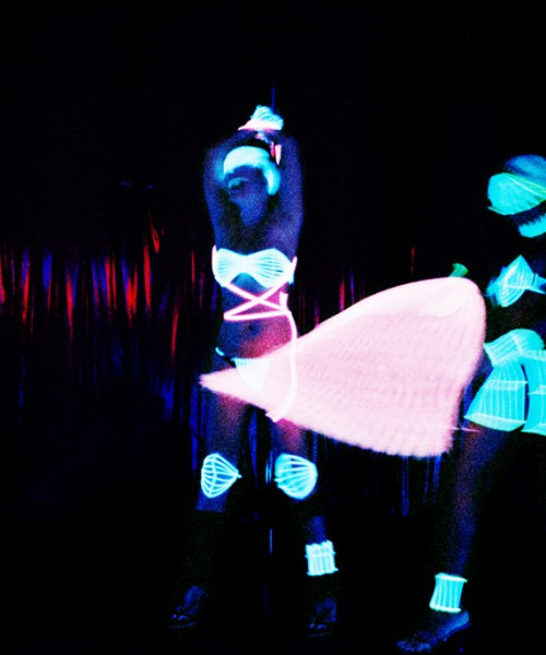 Two women dancing in a strip club. Their clothes shine in green neon light in the dark background.