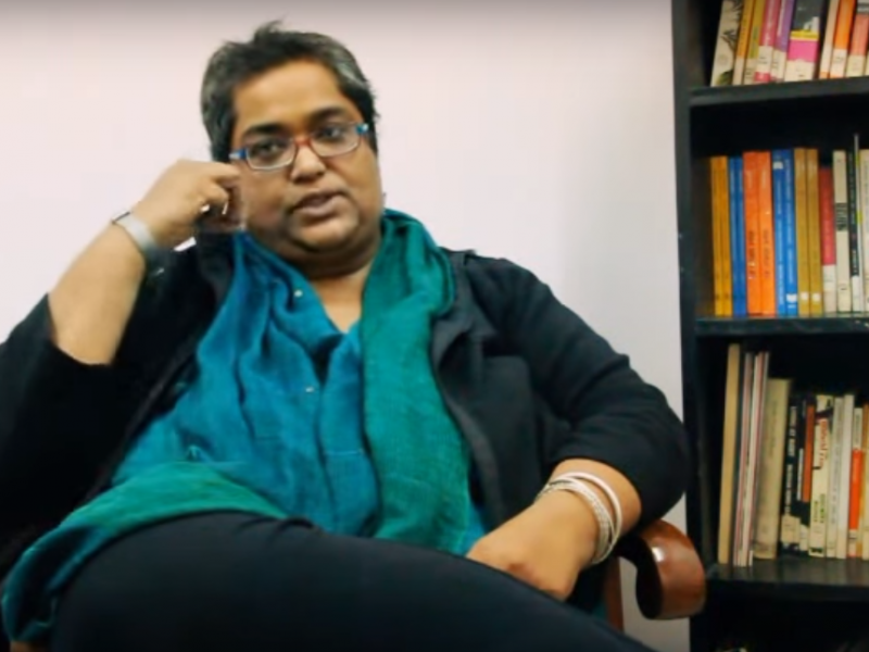Picture of feminist activist Pramada Menon. She has short hair and glasses, and is wearing a black kurta and green dupatta
