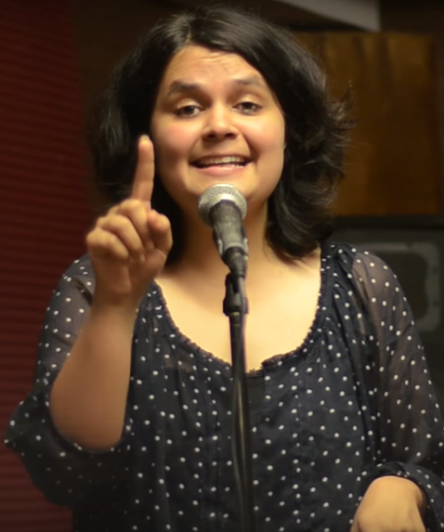 Picture of Priyam Redican standing in front of a mic. She is wearing a black top and has short shoulder-length hair