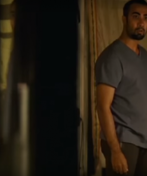 A man in a grey tee shirt and black pajamas standing, looking surprised at something.